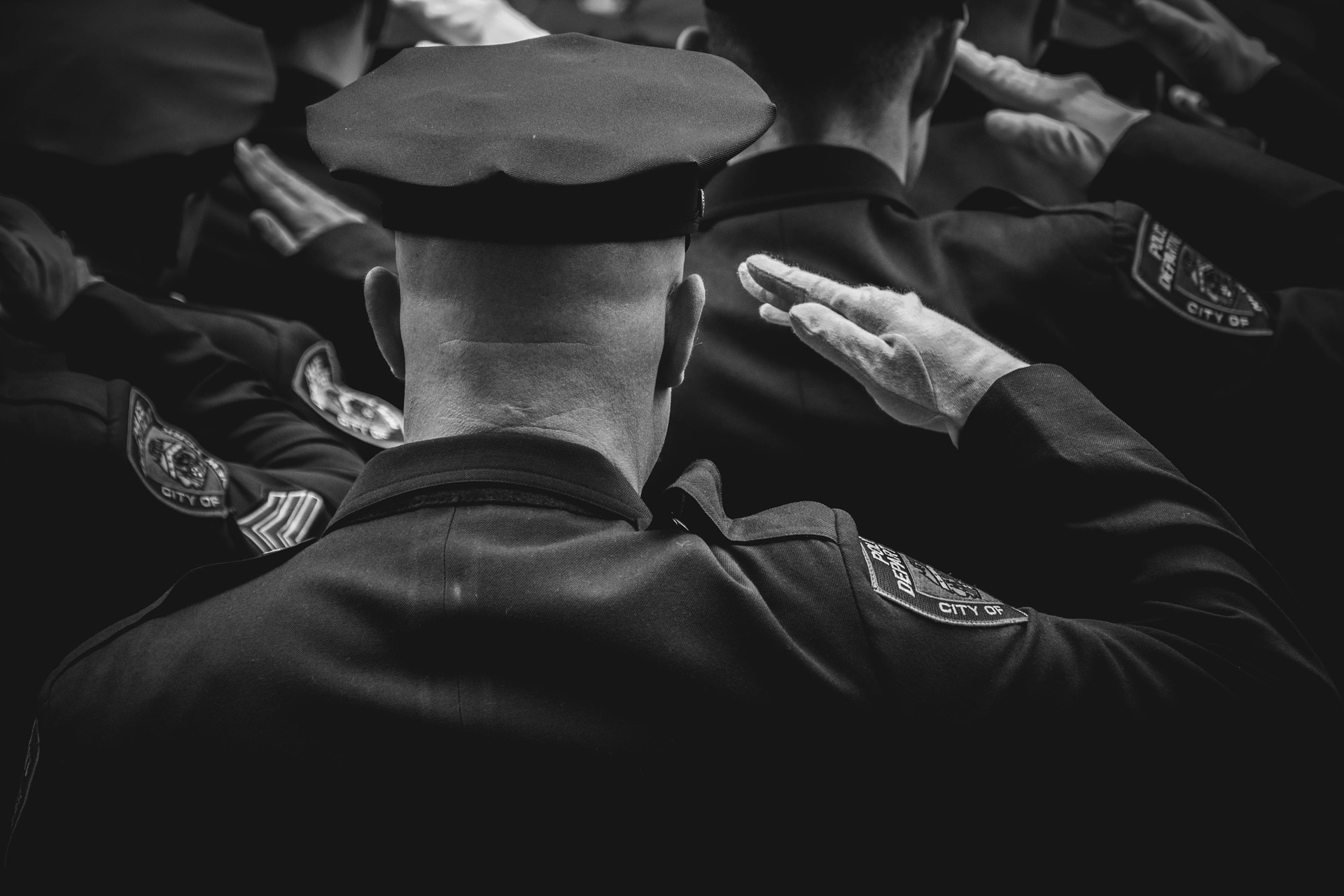 behind view of police officer saluting in a line of police offers