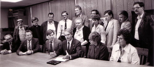 Wisconsin Governor Tony Earl signs legislation to provide for advance notice to workers  in case of a plant closing. Darryl viewed on the left of the Governor and Future  Milwaukee mayor, John Norquist, in second row.  Photo: Joanne Ricca.