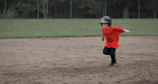 young boy running bases