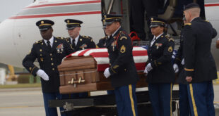 Marine in casket being lifted from jet plane