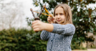 young girl using a slingshot