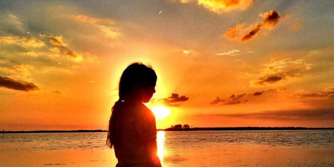 girl standing in front of sunset