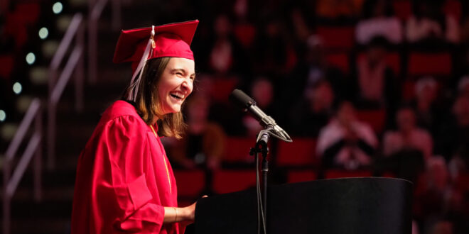 young woman laughs during graduation speech