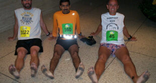 3 barefoot runners sitting after race