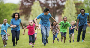 group of kids running with encouragement from adult