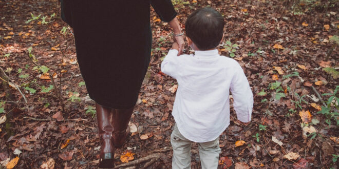 woman holding a young boy's hand