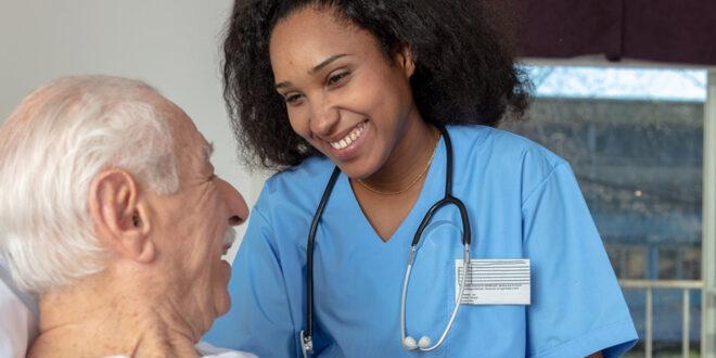 nurse smiling at old man in hospital