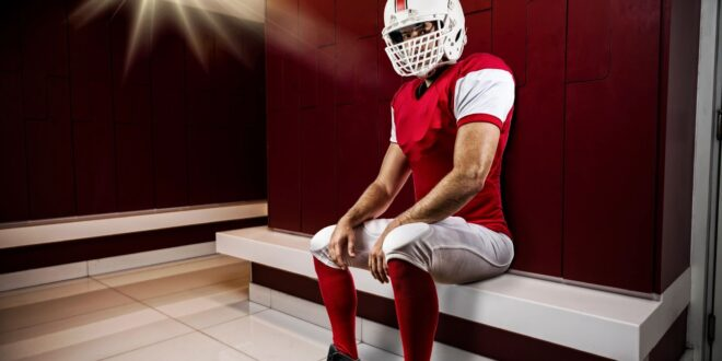 Football player sitting in locker room