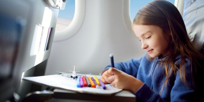 young girl sitting on plane