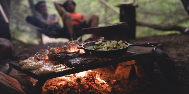 Camp fire grill with people telling funny stories