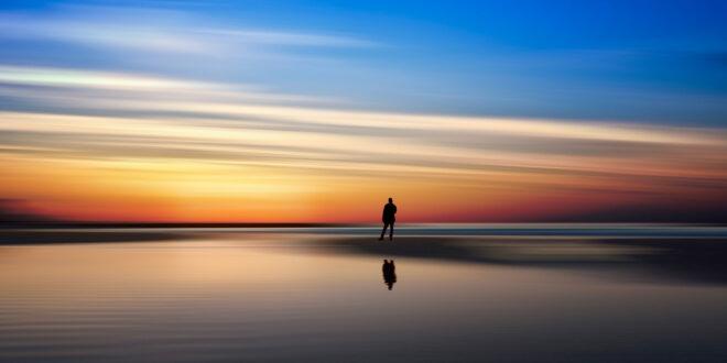 man at shoreline at sunset