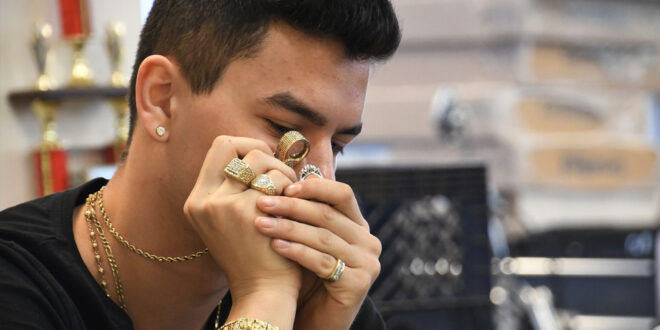 pawn broker looking at jewelry
