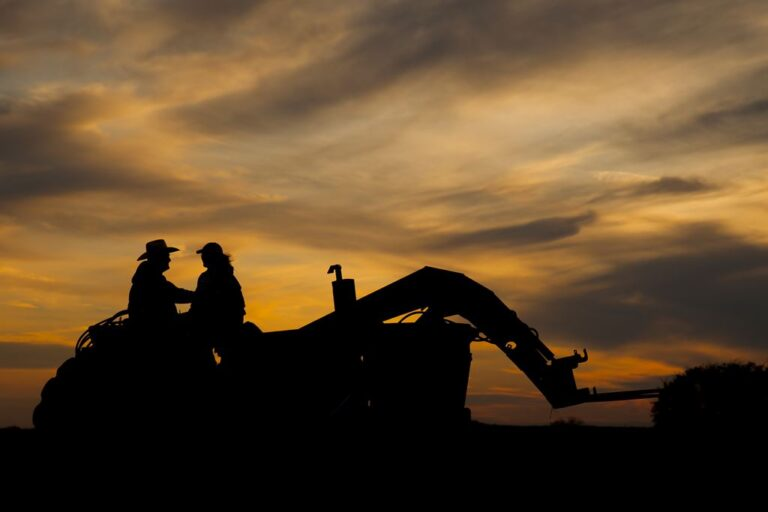 a couple sits on a tractor at sunset