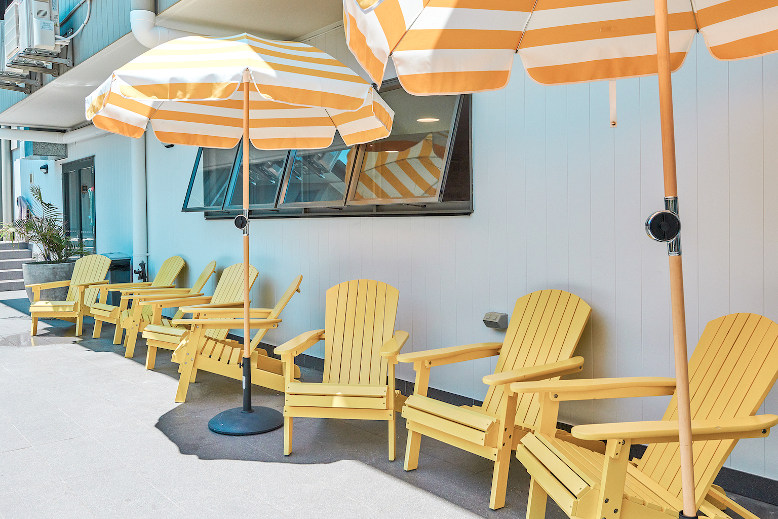 Outdoors chilling on yellow adirondack chairs at The Surf House in Byron Bay. Image: Amy Whitfield