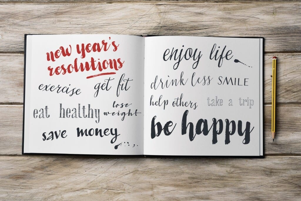open journal on rustic table writing new year's resolutions
