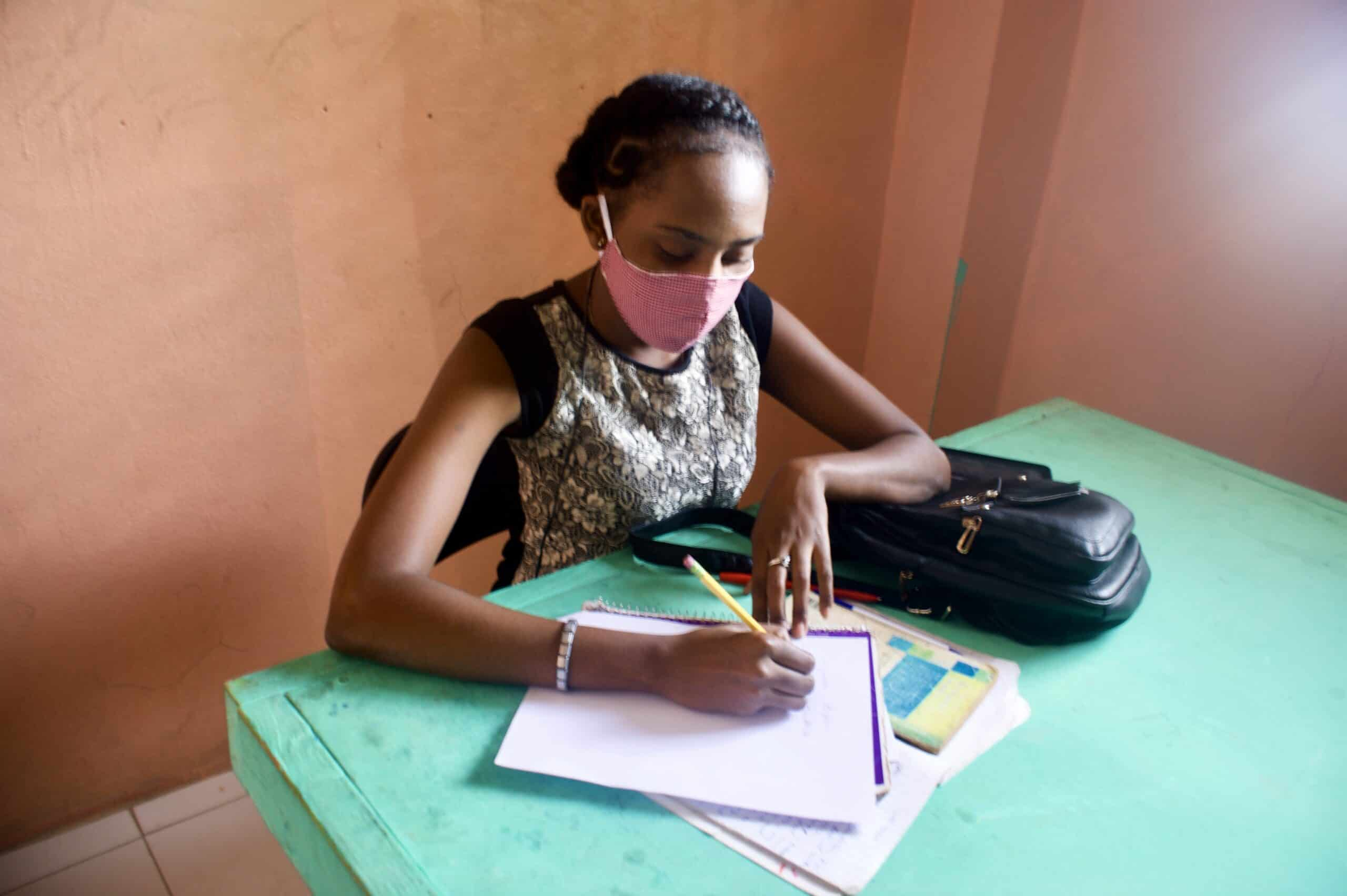 An empowered student with a mask works at an old, wooden, green desk with pencil and paper