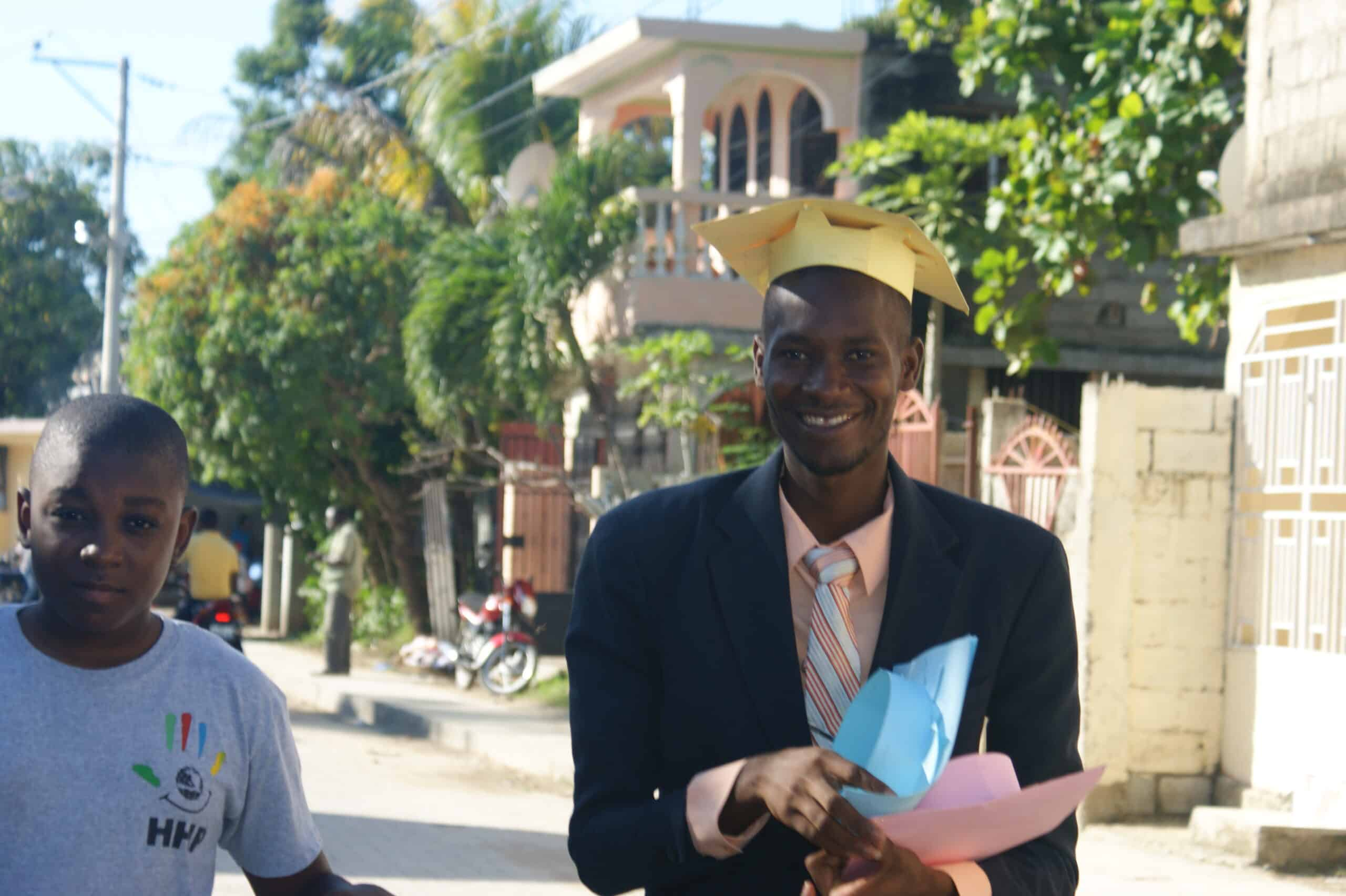 Two students prepare for graduation by distributing caps to others