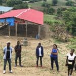 Empowered students stand near base of a farm