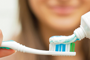 Woman putting toothpaste on a toothbrush