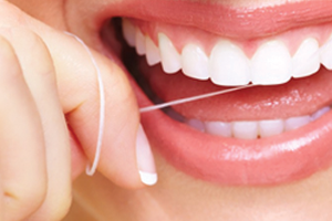 Woman flossing her white and straight teeth