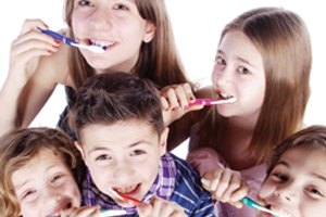 5 children brushing their teeth together and practicing good dental hygiene