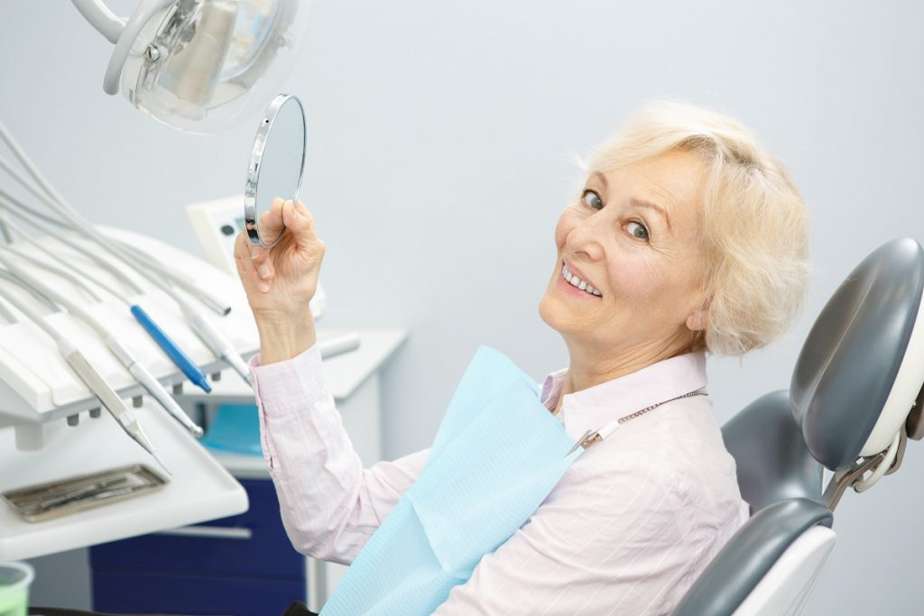 A patient at Cobblestone Park Family Dental admiring her dentures