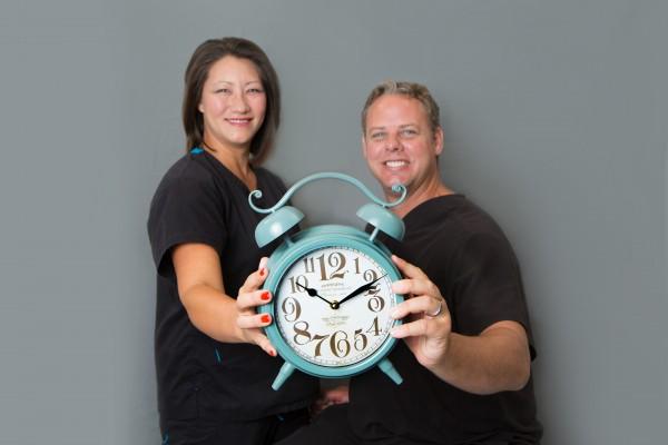 Dentists at Cobblestone Park Family Dental in Oklahoma City holding an alarm clock