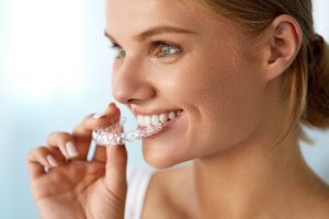 Women placing invisalign tray in her mouth