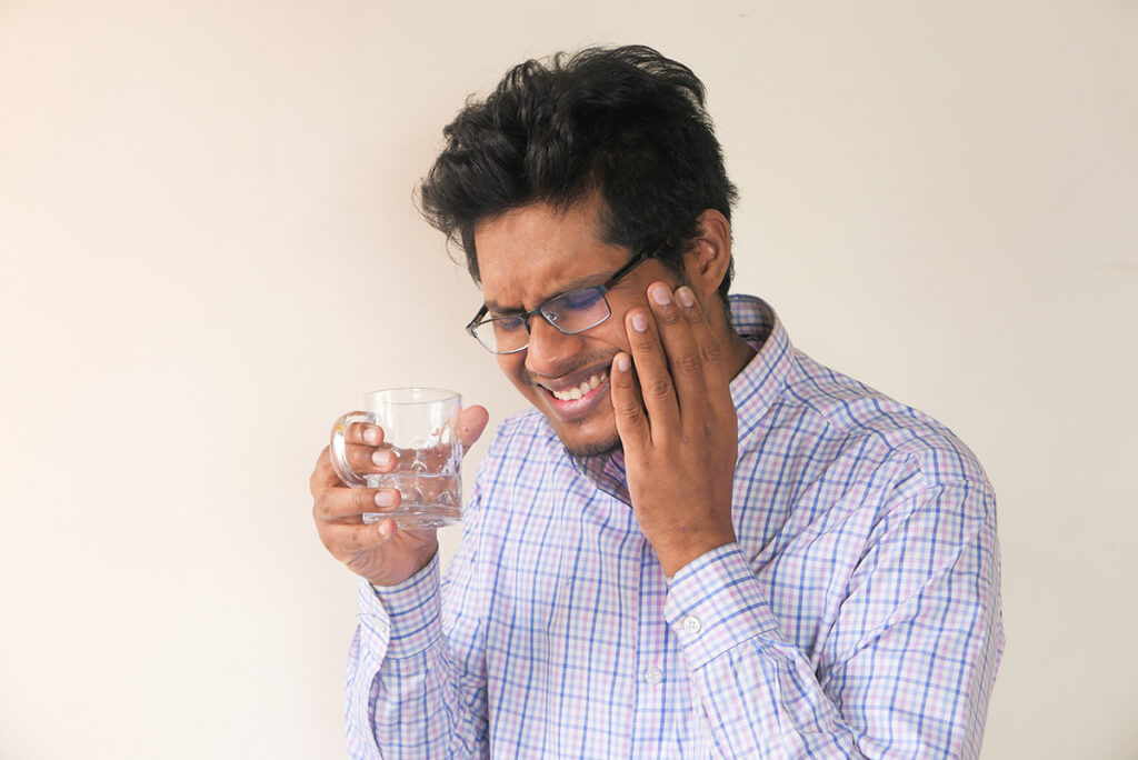 Man with sensitive teeth drinking water
