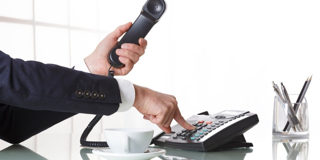 Hand of a businessman with dark gray suit holding the receiver of a black landline telephone while firmly pressing a button on telephone, with a cup of coffee and pens on a white office table. Concept of business and communcation.