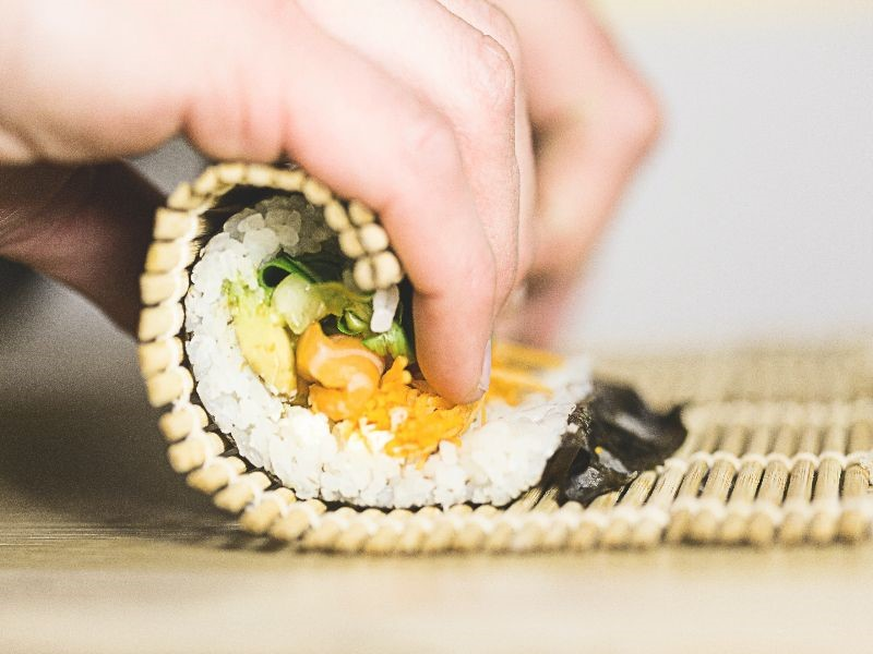 Someone rolling sushi