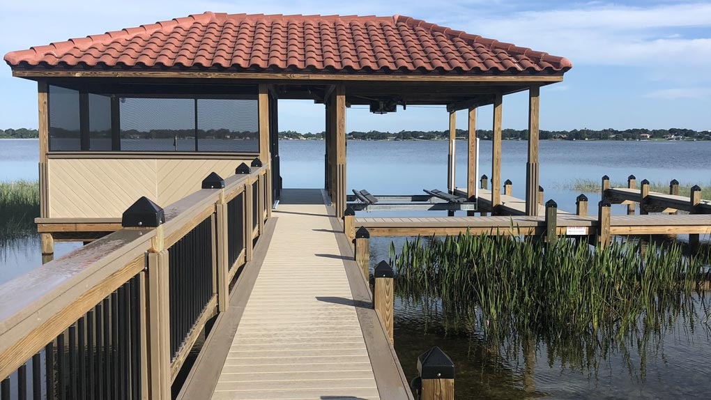 Photo of deck with wood railing to dock with wood railing and arbor with clay tile roofing