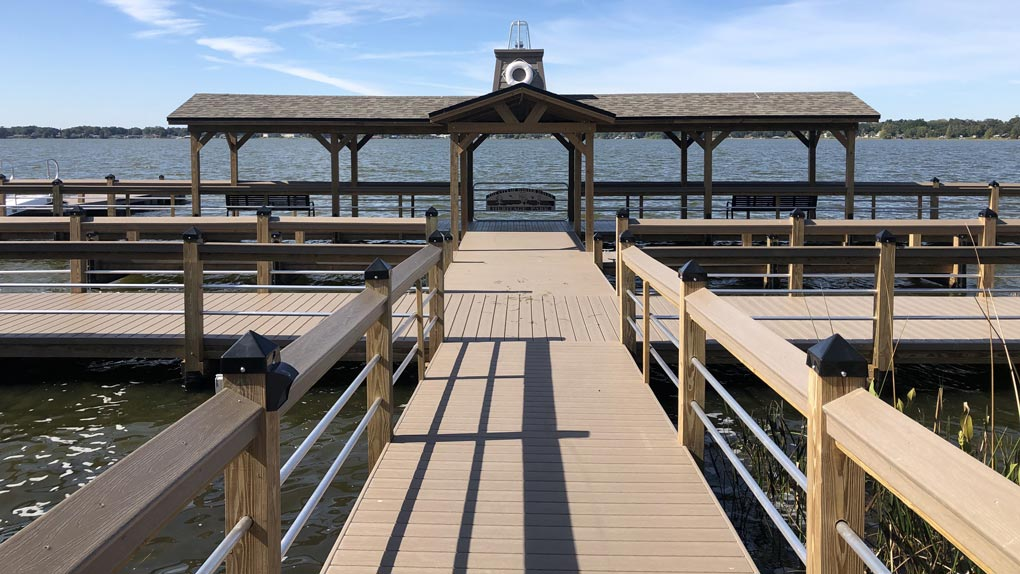 Photo of deck with wood railing to dock with wood railing and arbor