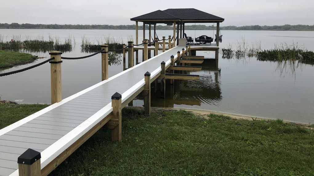 Photo of deck with rope railing to dock with arbor