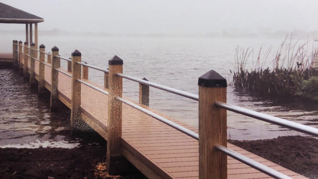 Photo of deck with metal railing to dock with arbor