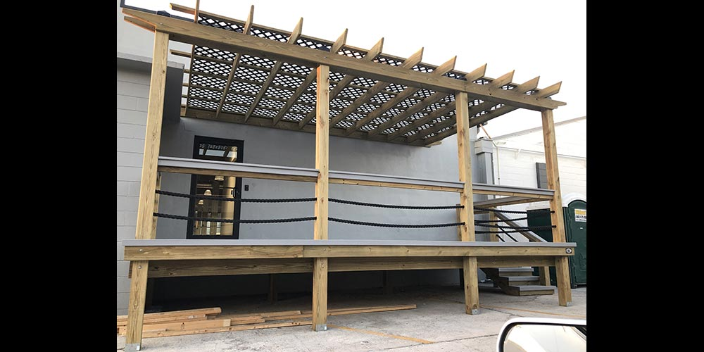 Photo of backyard deck with wood railing, arbor and stairway