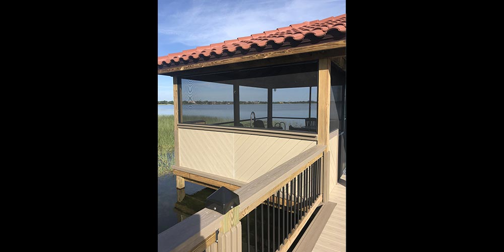 photo of deck with wood railing to dock with arbor and terracotta roofing