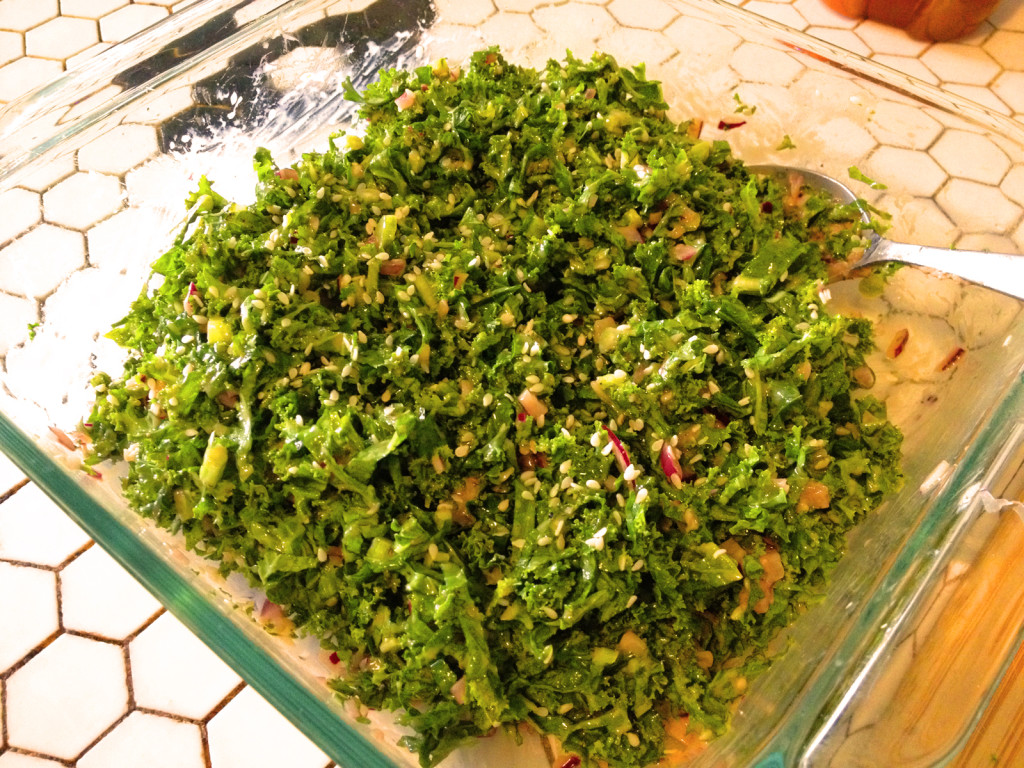 Mix the sesame honey Dijon dressing with the kale to ensure even coverage. Photo © Ben Young Landis.