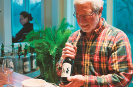 Clyde-Housel-displaying-a-bottle-of-Hiddencroft-wine