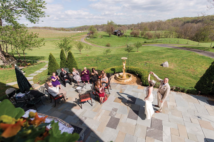 The bride and groom dance while overlooking the vineyard.