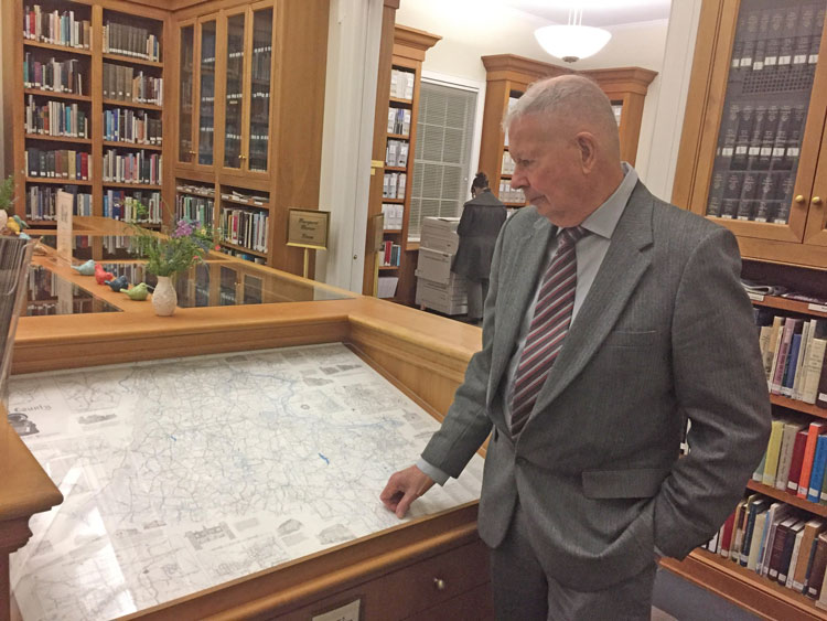 Eugene Scheel looks at his 1990 hand drawn map of Loudoun County inside Thomas Balch Library in downtown Leesburg.