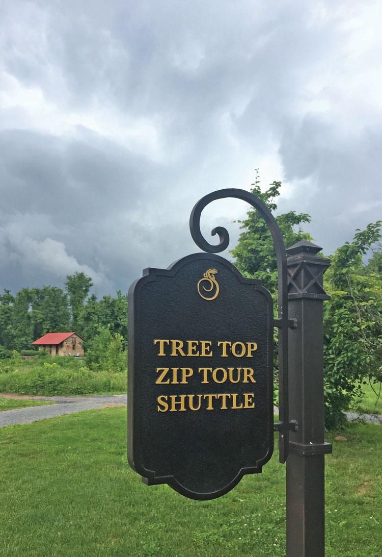 Tree top zip tour shuttle sign.