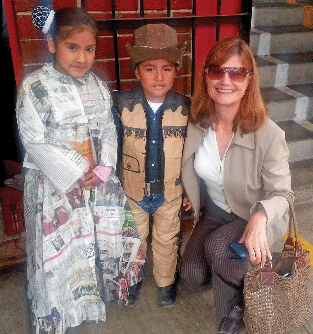 Dr. Linda Pfeiffer, founder of INMED Partnerships for Children with two children in Peru dressed in traditional costumes that they made. in 2015, INMED implemented deworming and aquaponics in the region of Callao, the chief seaport of Peru.