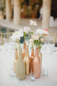 DIY painted rose gold painted wine bottles with flowers inside on table.