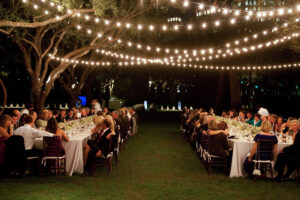 Night wedding with tables sat outside under string lights.