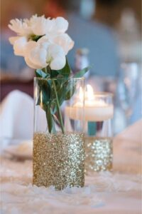 Glass vase with gold glitter with flower and tea light used as DIY wedding decorations on table.