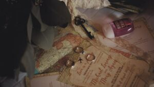 Close up on wedding invitations that show a map. These are on a table with hand sanitizer, key and rings.