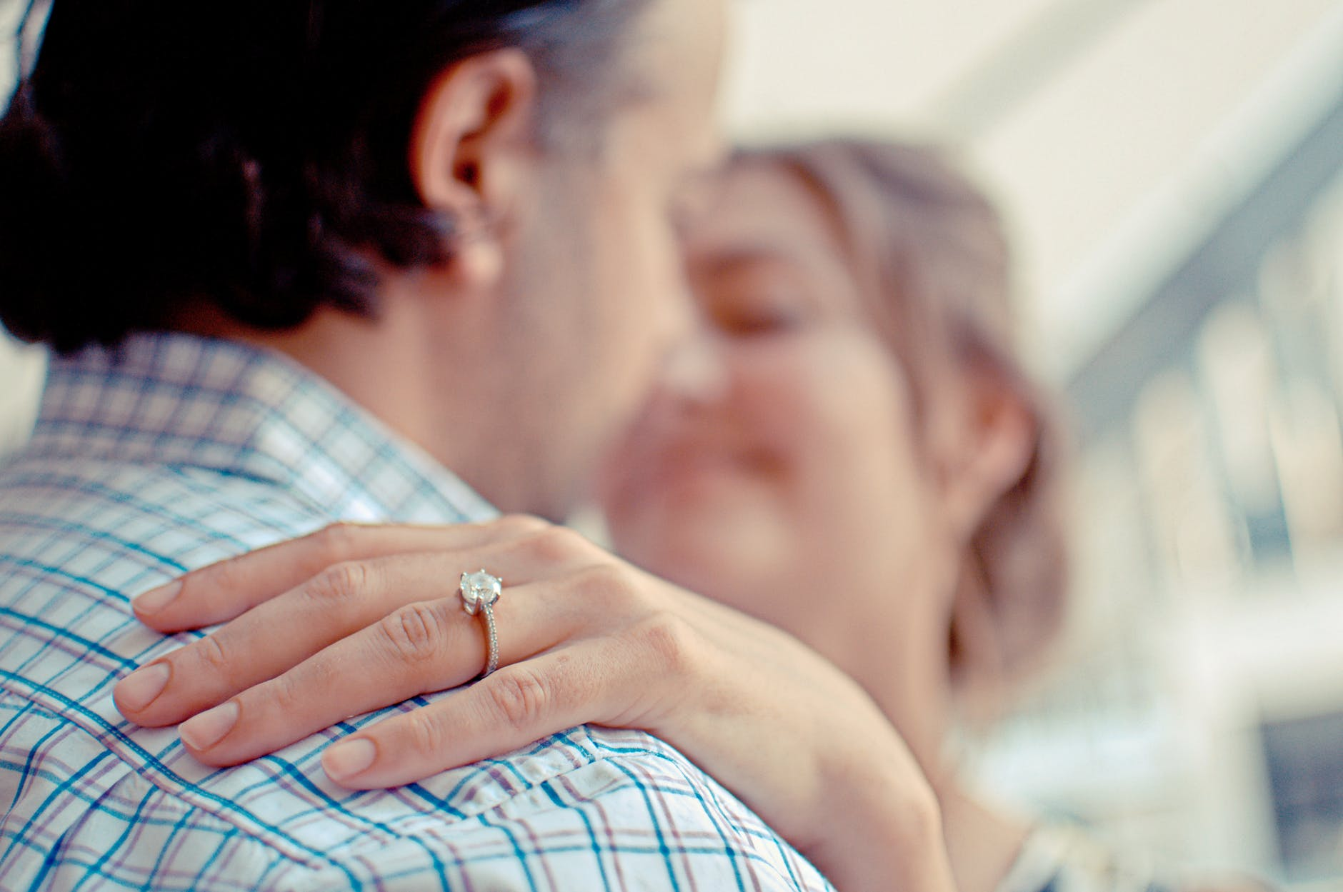 Ladies hand with engagement ring on resting on mans shoulder.