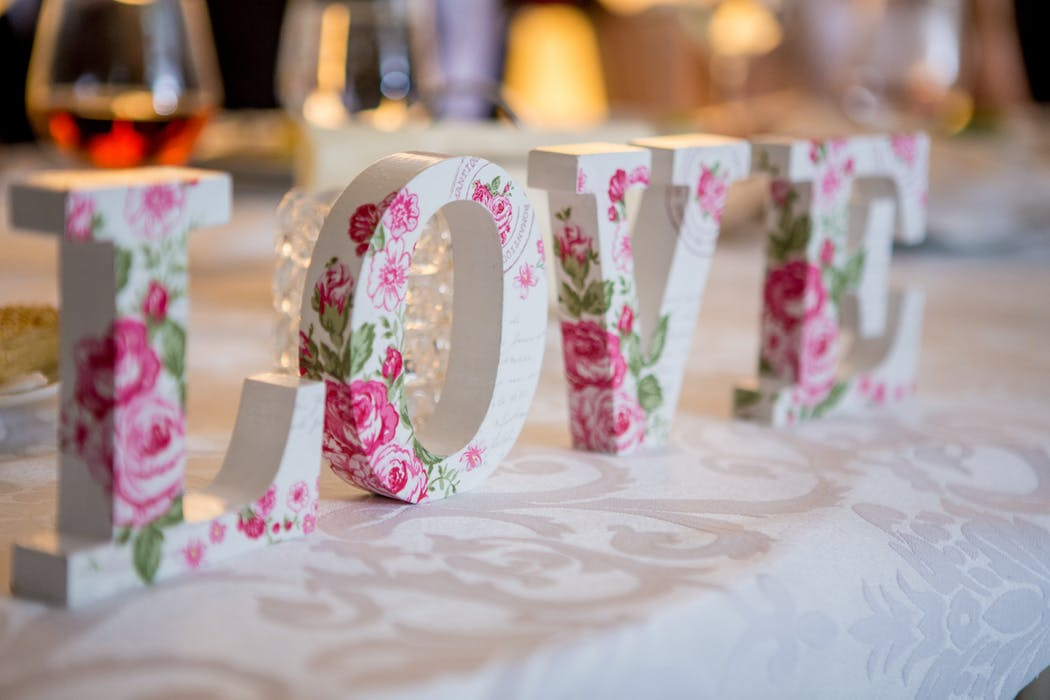 """Wooden letters that read """"love"""" with roses painted on them."""