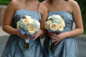 Bridesmaids in slate blue dresses holding flowers.